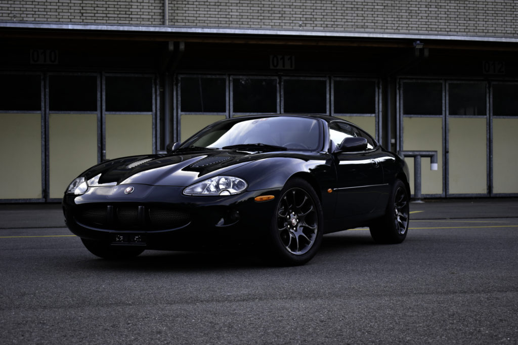 British Racing Green 2000 Jaguar XKR 4.0 Supercharged Coupe Youngtimer vor Lagerhallen in Frontansicht