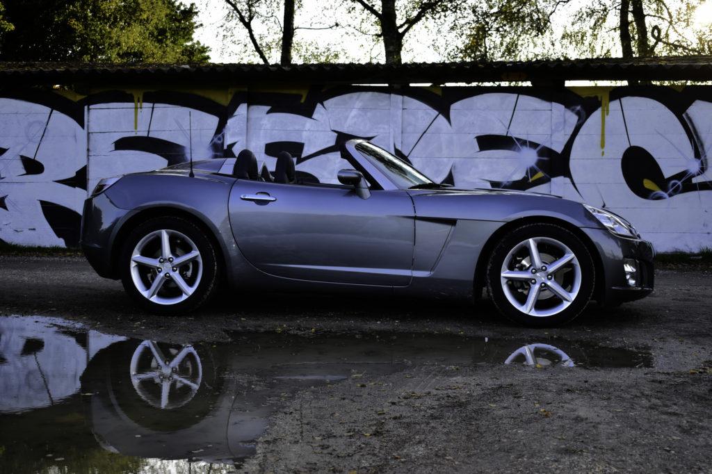 Silberner 2007 Opel GT 2.0 Turbo 2. Generation Liebhaberfahrzeug Seitenansicht rechts vor Wand mit Graffiti Streetart