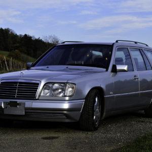 Silberfarbener 1992 Mercedes_Benz 320 TE Youngtimer Liebhaberfahrzeug Alltagsklassiker in Rebberg in Dreiviertelansicht von vorne links