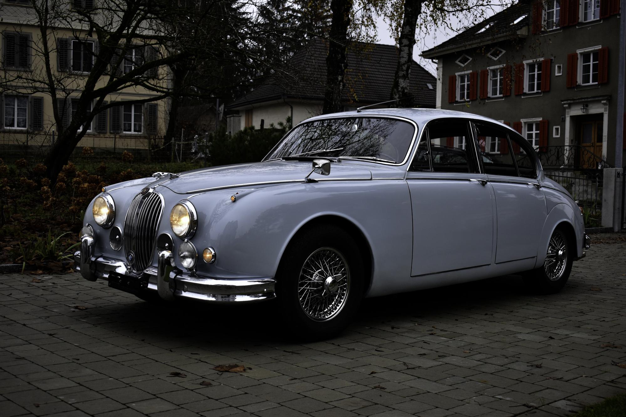 Versteigerung Auktion hellblauer 1965 Jaguar Mark 2 2.4 Liter in Dreiviertelansicht von vorne links mit Dorfbild im Hintergrund