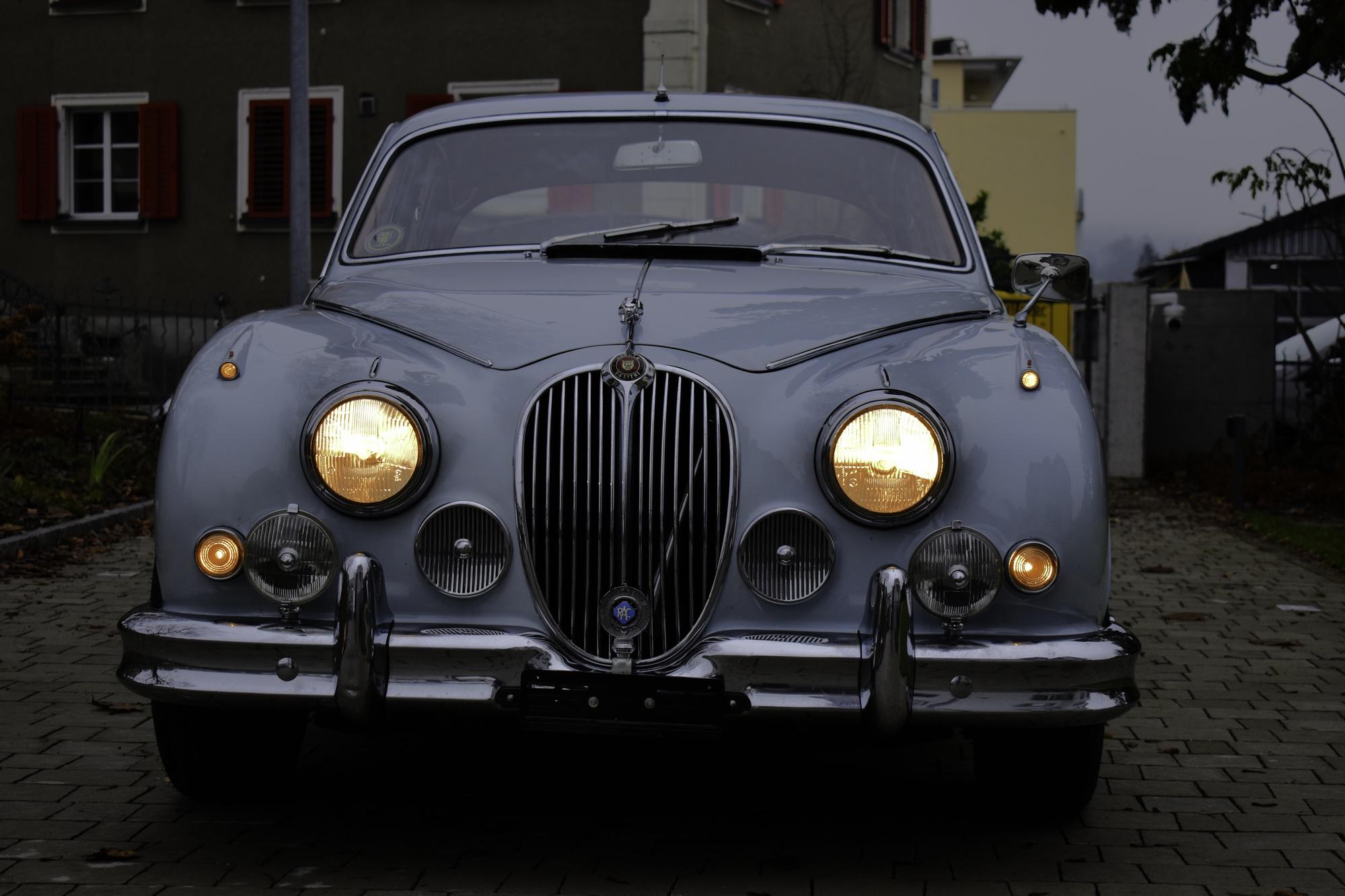 Hellblauer 1965 Jaguar Mark 2 2.4 Liter Oldtimer Veteranenfahrzeug in Dreiviertelansicht von vorne links mit Bäumen und Dorf im Hintergrund