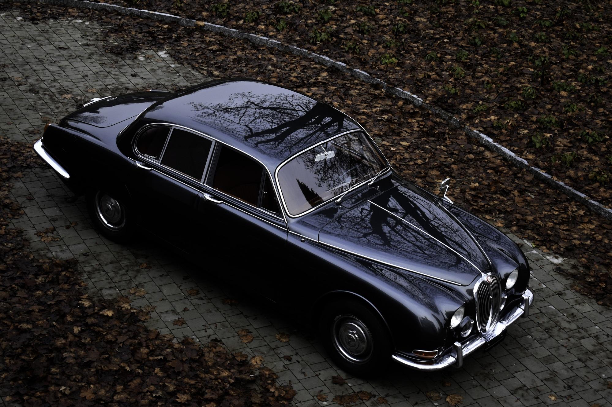 Dunkelgrauer 1966 Jaguar S-Type 3.8 Litre Oldtimer Veteranenfahrzeug in Dreiviertelansicht von vorne oben rechts