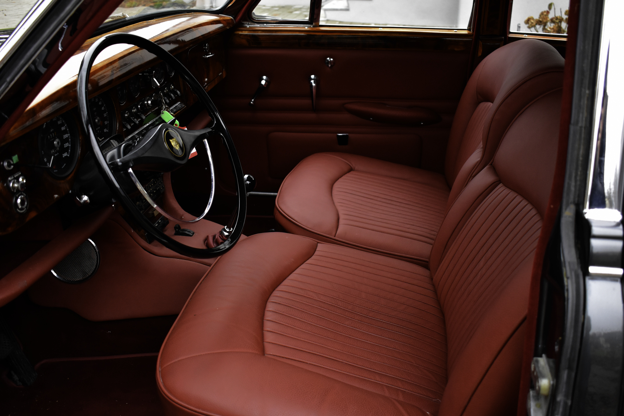 Interieur eines dunkelgrauen 1966 Jaguar S-Type 3.8 Litre Oldtimer Veteranenfahrzeug mit den roten Vordersitzen und dem Armaturenbrett fotografiert durch die offene Fahrertüre