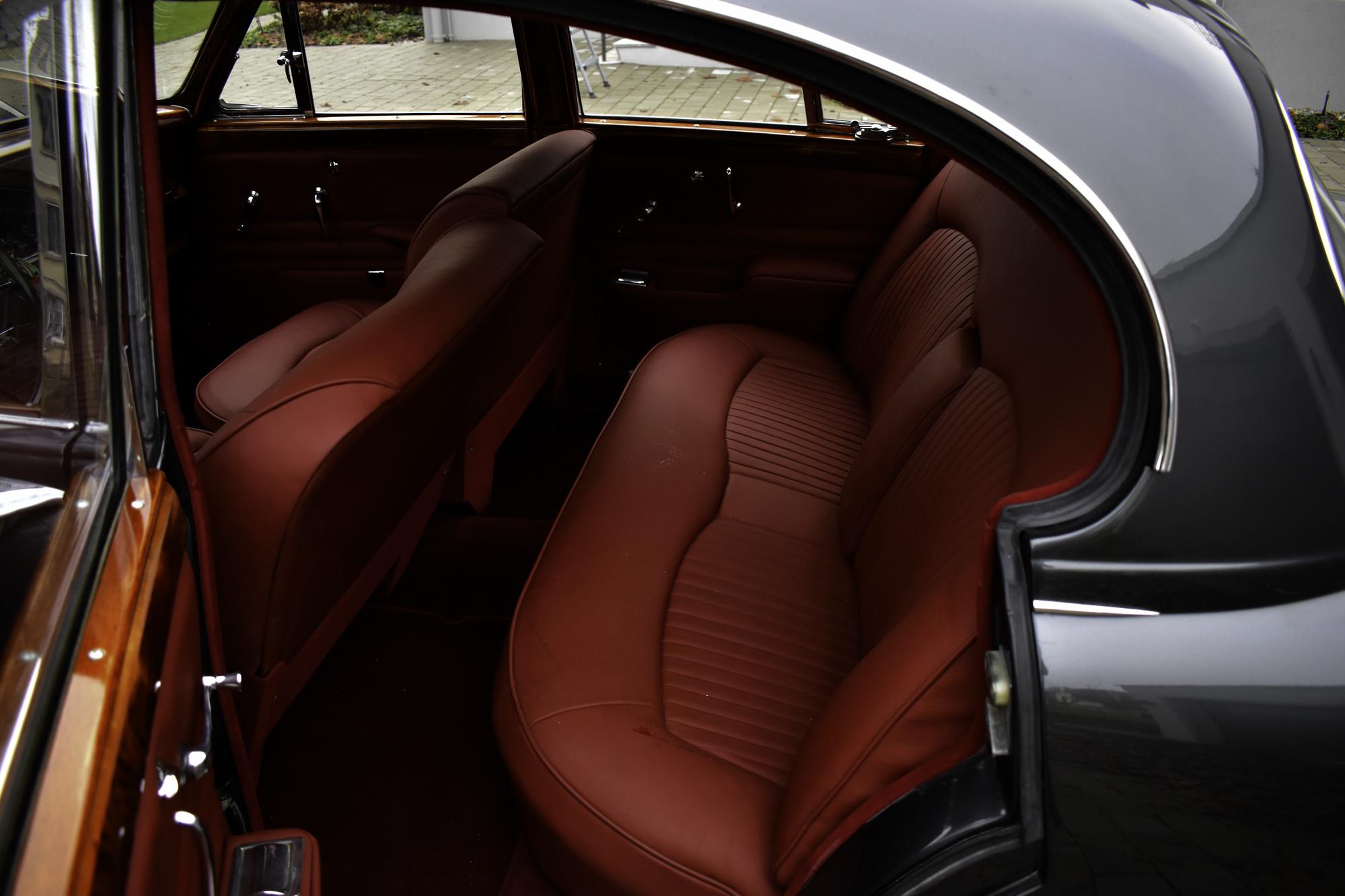 Interieur eines dunkelgrauen 1966 Jaguar S-Type 3.8 Liter Oldtimer Veteranenfahrzeug mit der mit rotem Leder ausstaffierten Rückbank fotografiert durch die offene Hintertüre links
