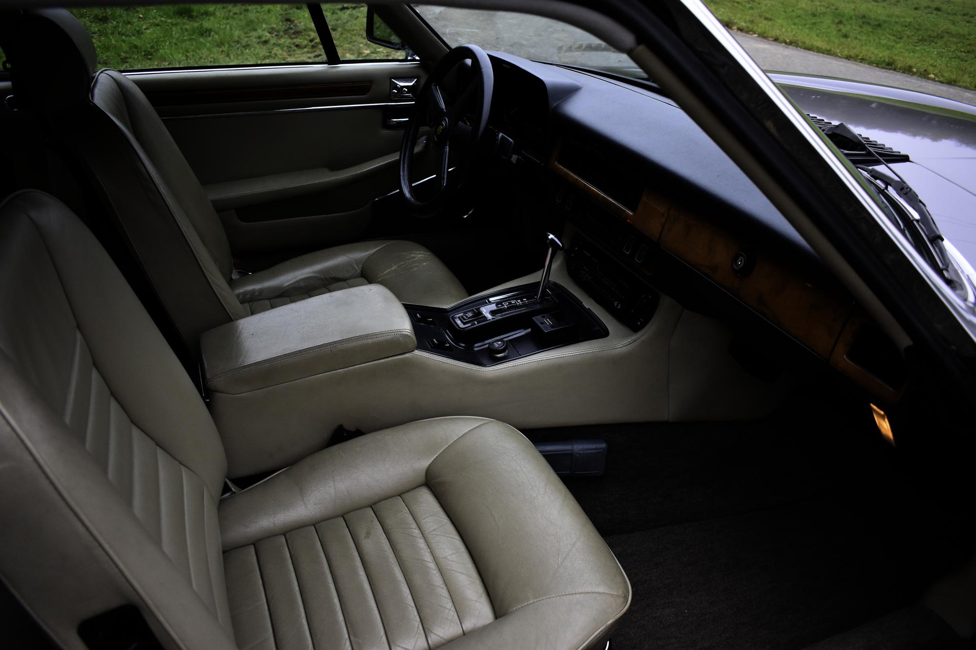 Grauer 1985 Jaguar XJS 5.3 V12 H.E. Coupe Oldtimer Veteranenfahrzeug mit Sicht ins Cockpit mit offener Beifahrertüre