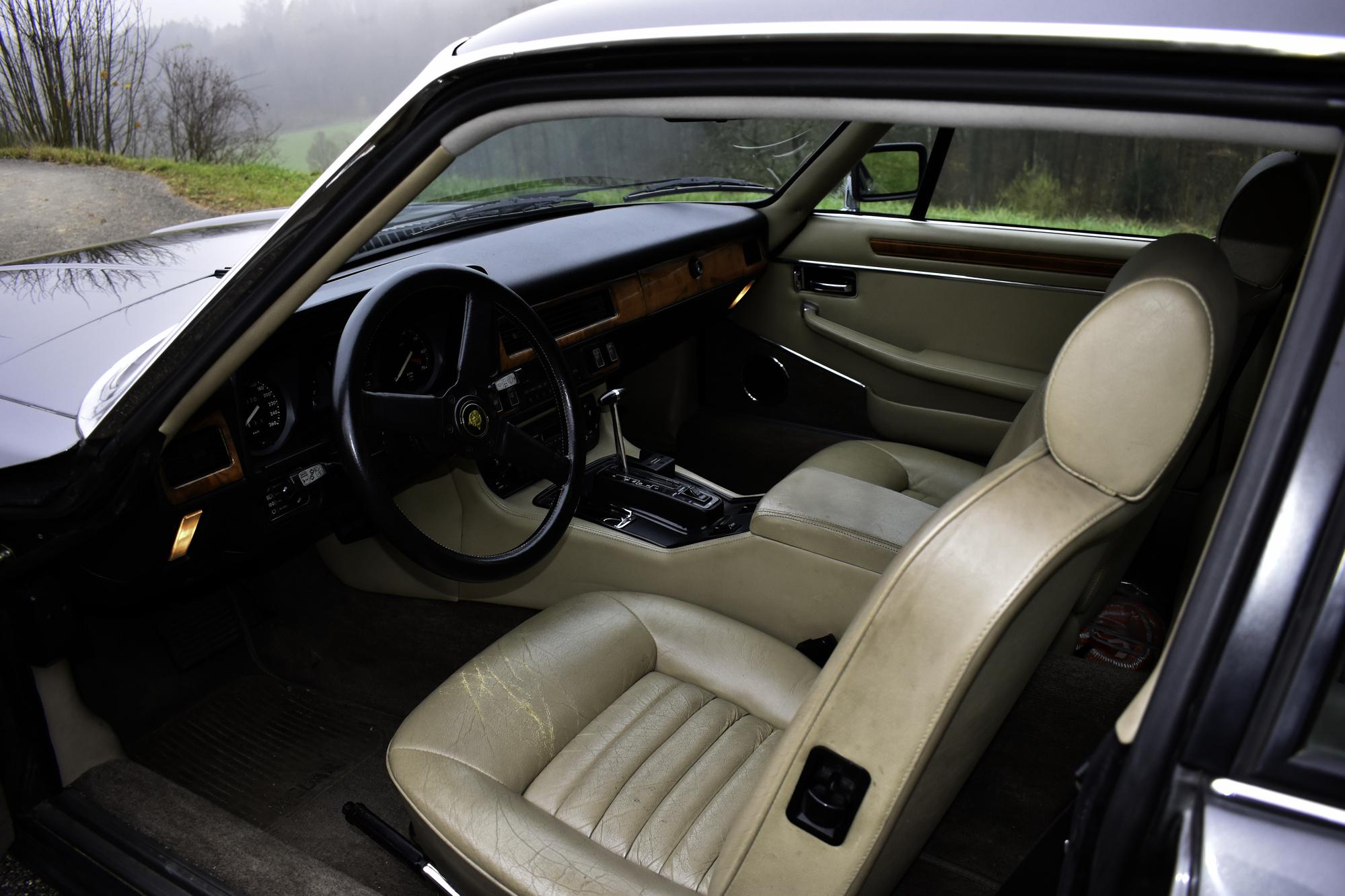 Grauer 1985 Jaguar XJS 5.3 V12 H.E. Coupe Oldtimer Veteranenfahrzeug mit Sicht ins Cockpit mit offener Fahrertüre