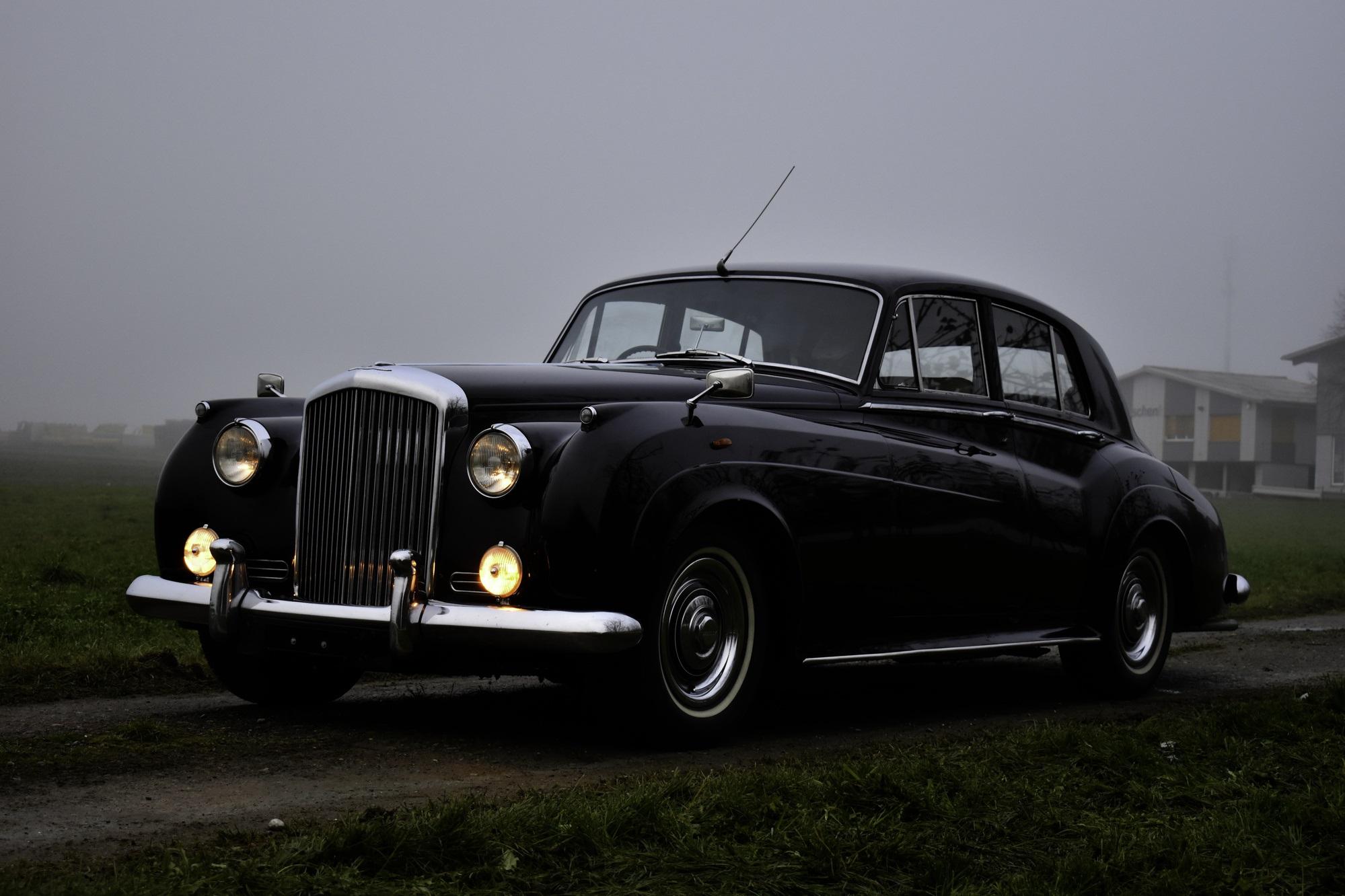 Versteigerung Auktion dunkelroter 1957 Bentley S1 in Dreiviertelansicht von rechts vorne im Nebel mit Baumhain im Hintergrund