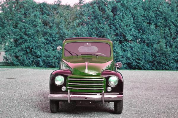 Rot-Schwarzer 1949 Fiat 500 C Topolino Veteranenfahrzeug Oldtimer in Frontalansicht vor einer grünen Hecke