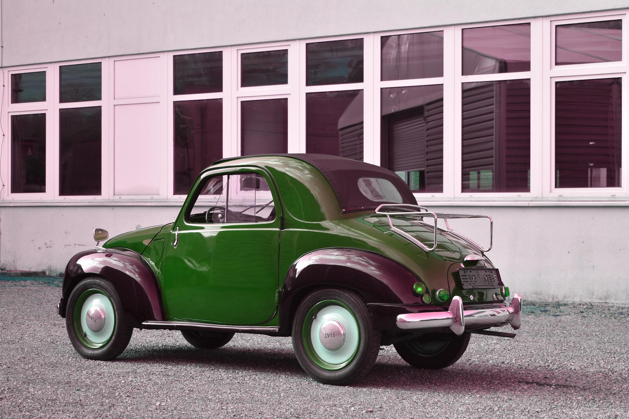 Schwarz-roter Fiat 500 C Tipolino von vorne mit Hecke im Hintergrund