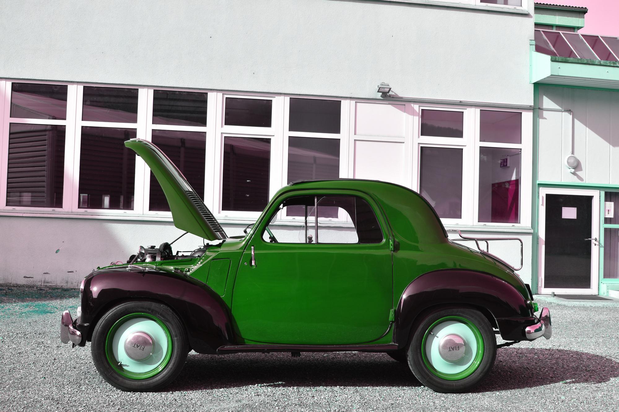 Schwarz-roter Fiat 500 C Tipolino aus 1949 mit offener Motorhaube in Seitenansicht vor Industriegebäude
