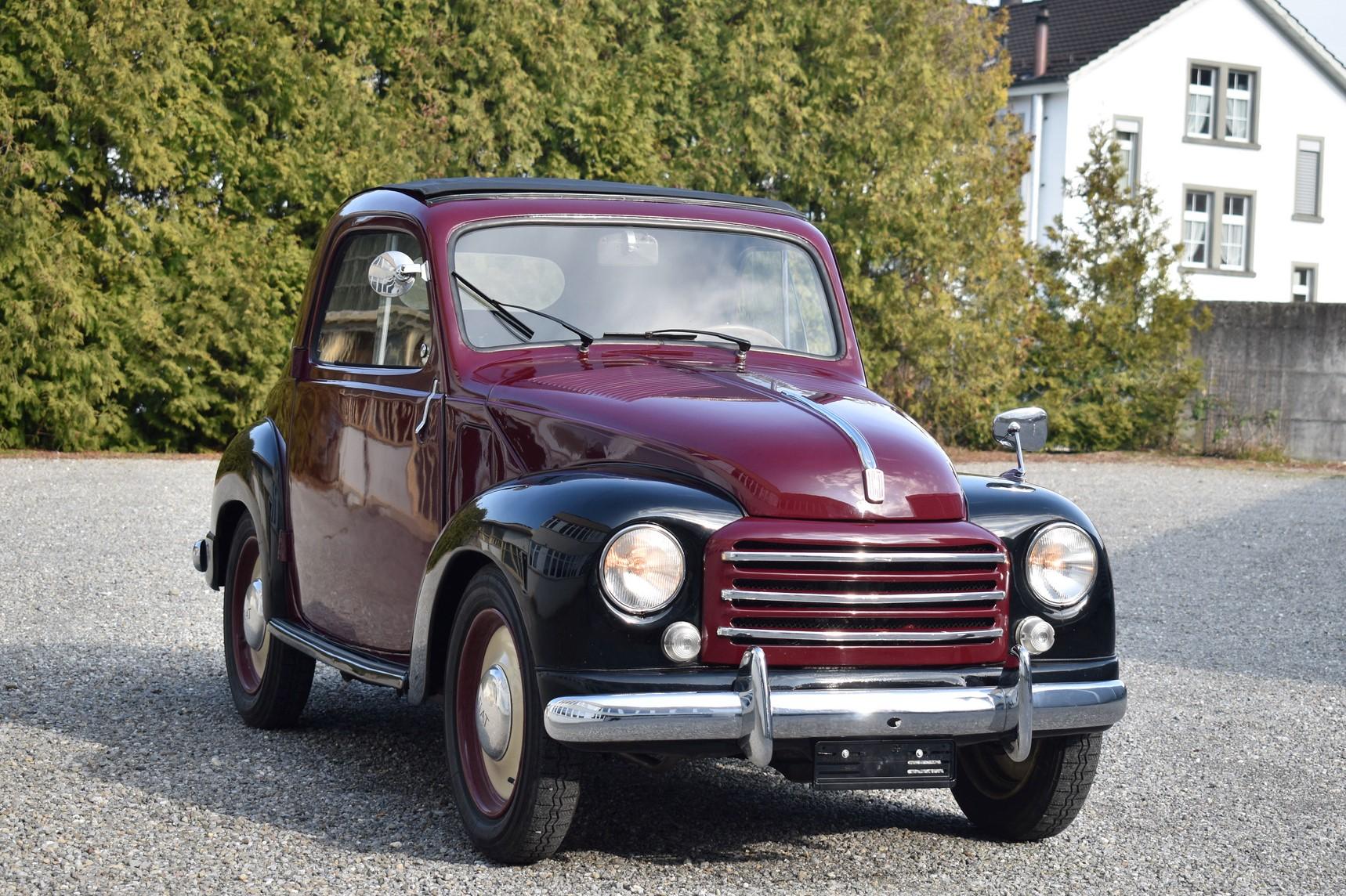 Rot-schwarzer 1949 Fiat 500 C Tipolino Veteranenfahrzeug und Oldtimer in Seitenansicht vor altem Fabrikgebäude