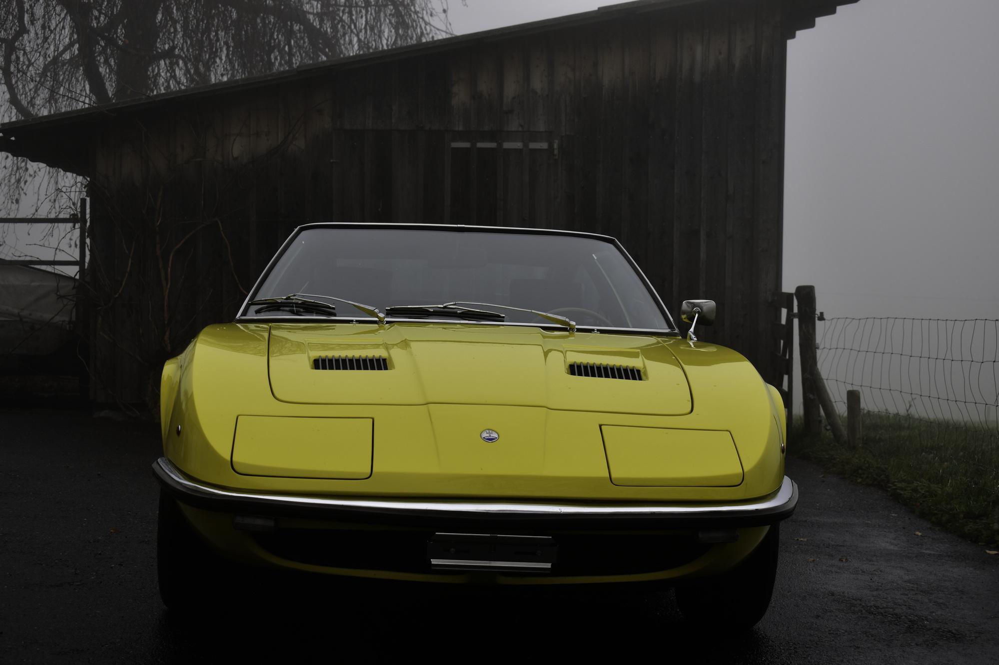 Gelber Maserati Iny 4200 4.2 Liter AM 116 mit schwarzem Interieur und Veteranenzulassung Oldtimer vor Holzschopf in Dreiviertelansicht von vorne rechts in nebliger Landschaft