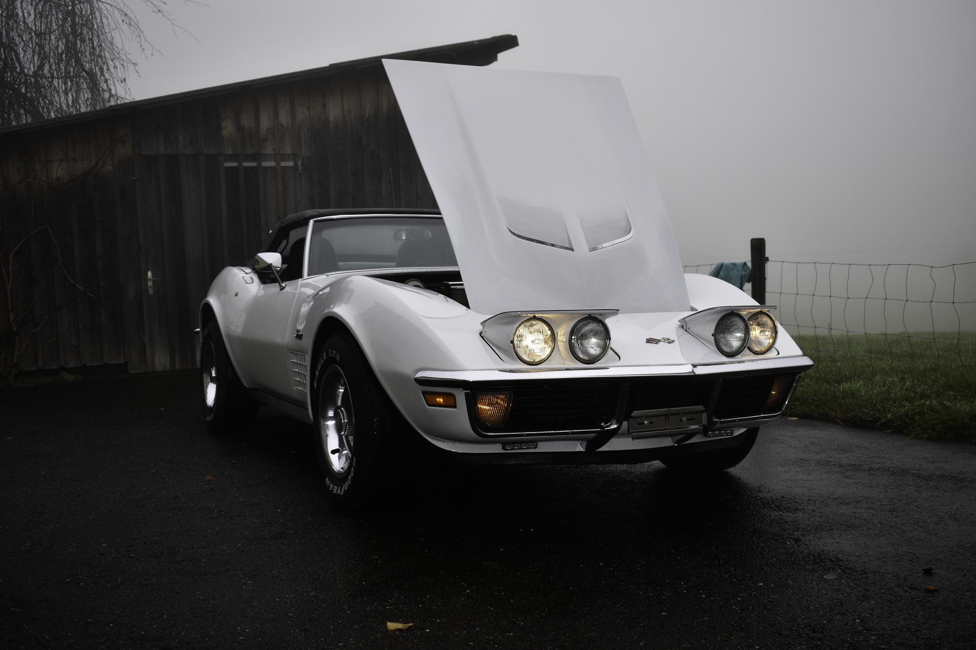 Weisse Chevrolet Corvette C3 Stingray 350 cuin 5.7 Liter 1971 in Seitenansicht mit aufgeklappter Motorhaube und Lichtern