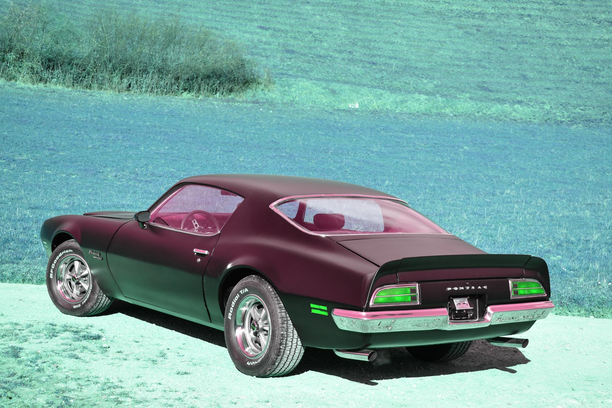 Mattschwarzer 1970 Pontiac Firebird Esprit Formula 350 5.7 Liter oldtimer in Dreiviertelansicht in grüner Wiese stehend
