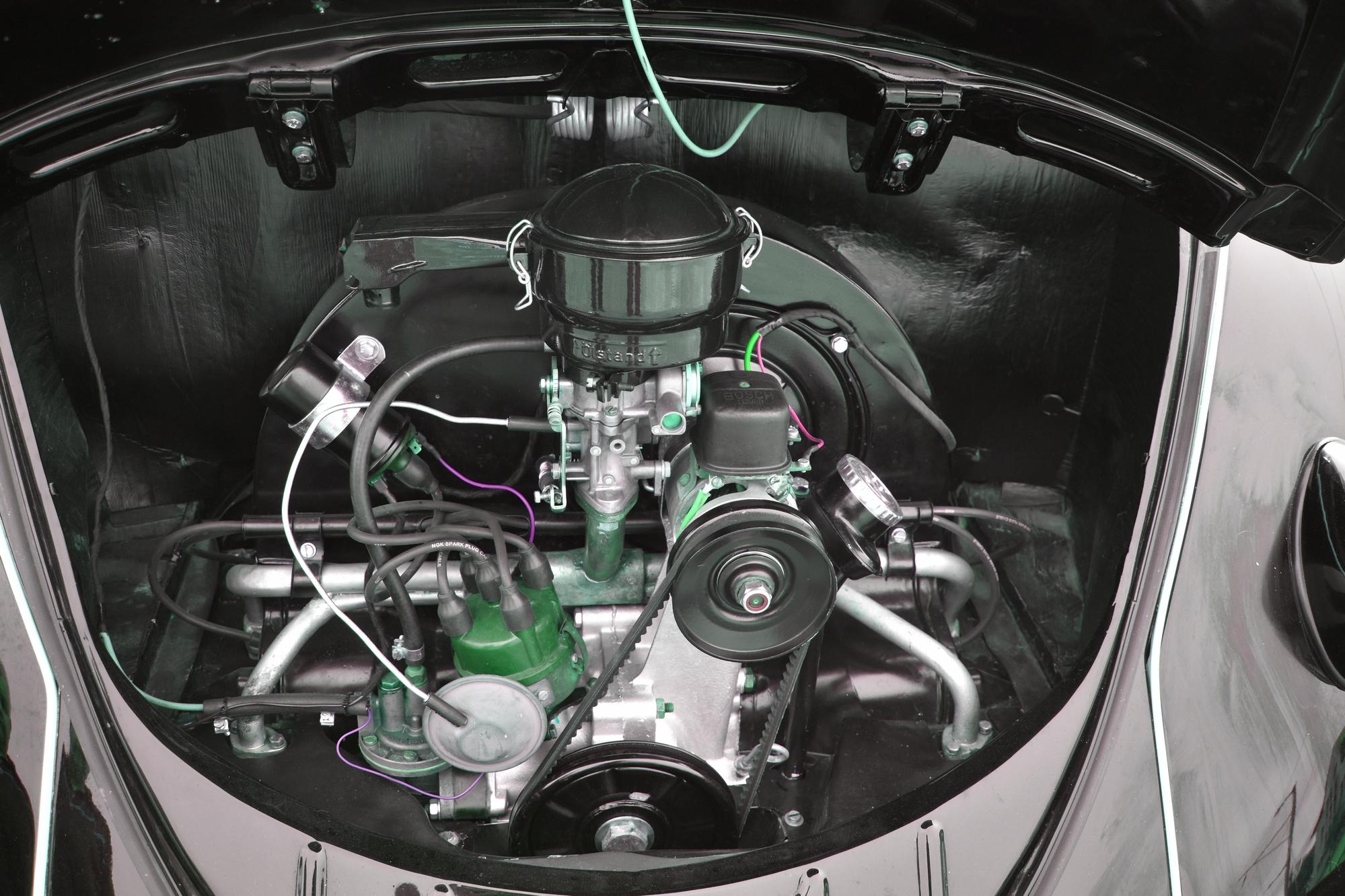 Luftgekühlter Boxermotor im Heck eines schwarz-rot lackierten VW Käfer Ovali Beetle Bug Typ 1 aus dem Jahre 1953
