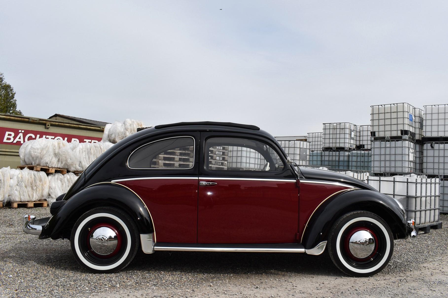 Schwarz roter VW Käfer Ovali Beetle Bug Typ 1 aus dem Jahre 1953 mit Faltdach in Seitenansicht vor Plastikcontainer mit Kiessplit