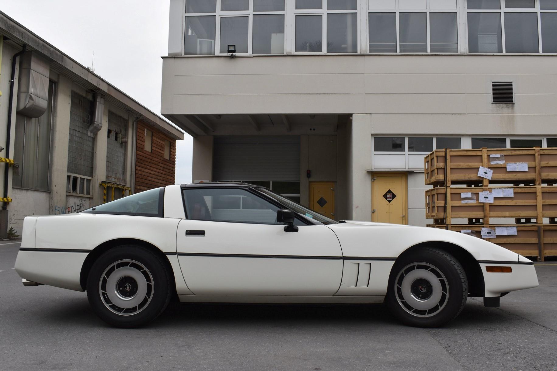 Weisse Chevrolet Corvette C4 Targa 350 cuin 5.7 Liter aus dem Jahre 1984 in Seitenansicht vor einem alten Industriegebäude