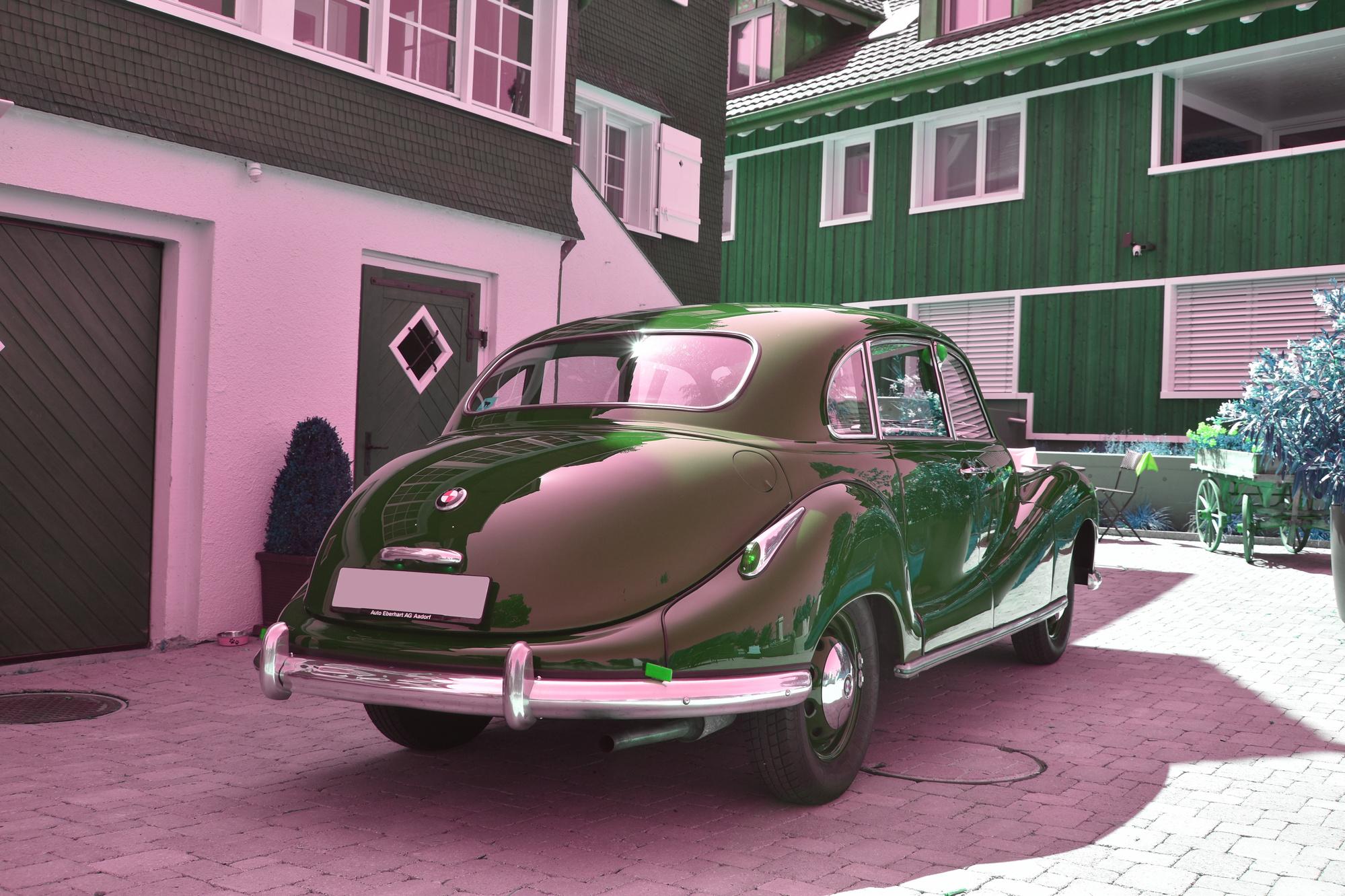 Maron-farbener BMW 501 A Oldtimer aus 1954 in Ansicht von hinten vor einem historischen Wohngebäude