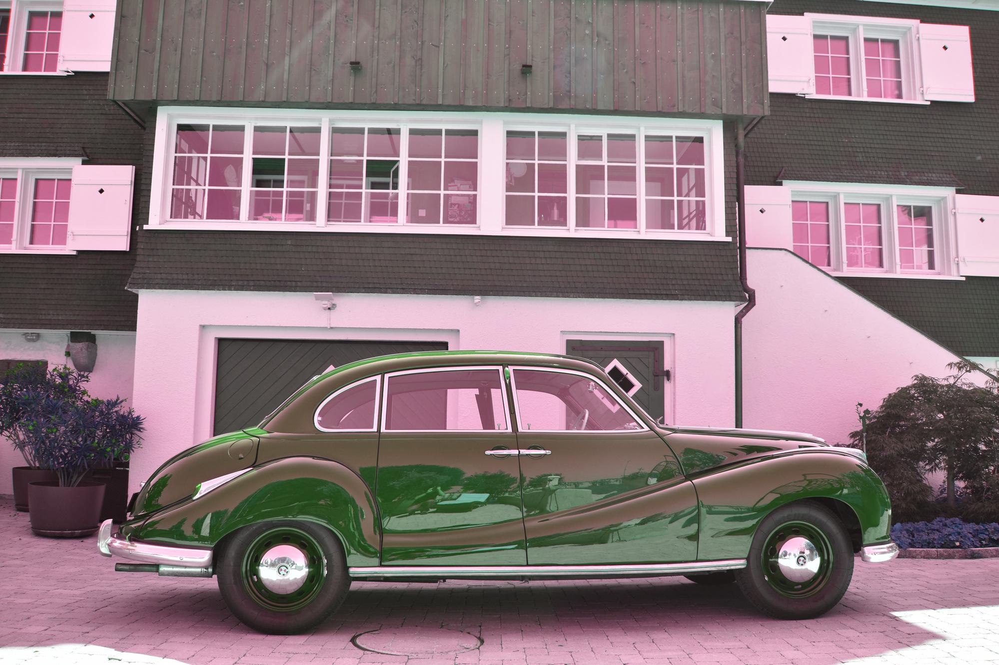 Maron-farbener BMW 501 A Oldtimer aus 1954 in Seitenansicht vor einem historischen Wohngebäude