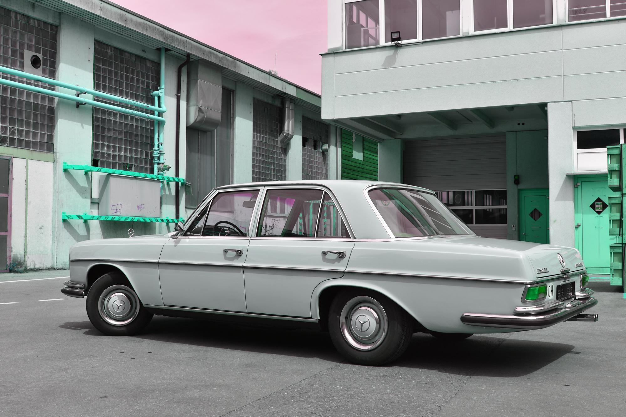 Ein Mercedes 250SE Veteranenfahrzeug in der Farbe hellbeige aus dem Jahre 1966 in Seitenansicht vor einem alten Industriegebäude