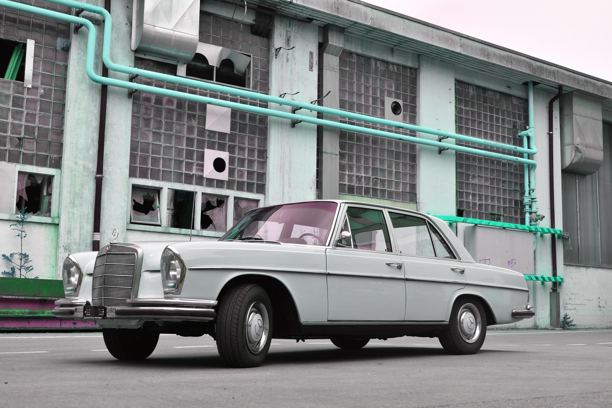 Ein Mercedes-Benz 250 SE Oldtimer in der Farbe hellbeige aus dem Jahre 1966 in Frontansicht vor einem in die Jahre gekommenen Industriegebäude