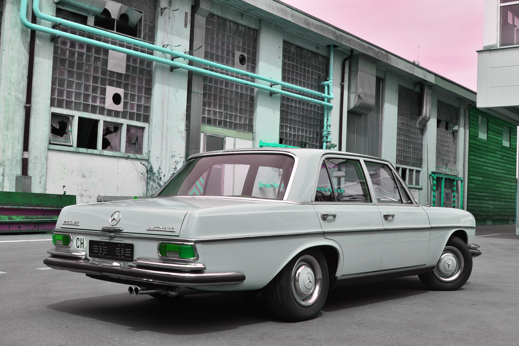 Mercedes-Benz 250 SE classic car (1966) in Rückansicht mit Industriegebäude im Hintergrund